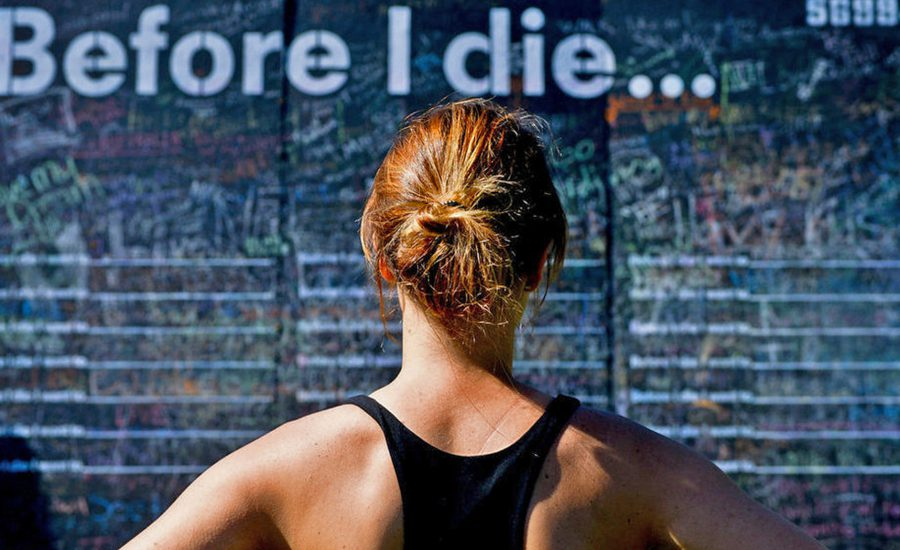 Woman looking at sign that says Before I Die