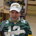 Packers fan wearing jersey and hat during rehab session
