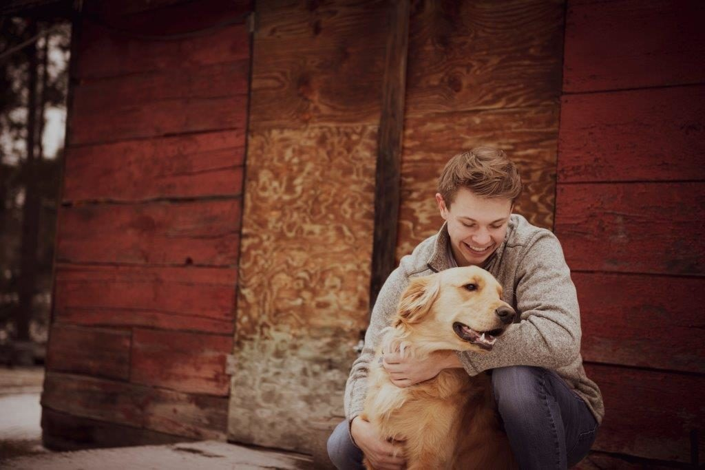 Dawson Hoffman and his dog Max in front of a barn